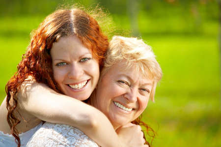 Embraces happy mothers with the adult daughter against a lawn