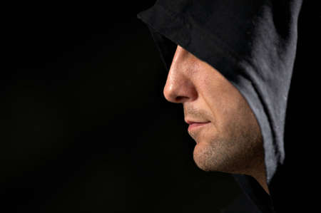 hooded: Profile of the man in a hood on a black background