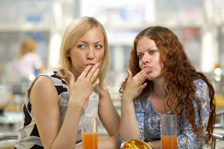 Girl-friends eat snack in cafe and lick fingers photo