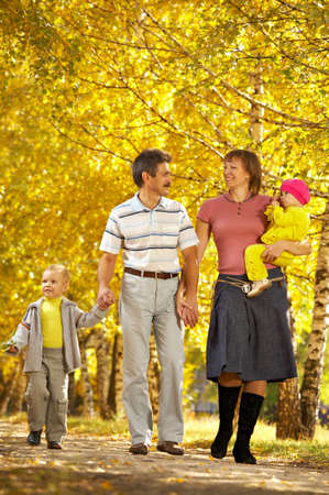 The family with two children walks on autumn park photo