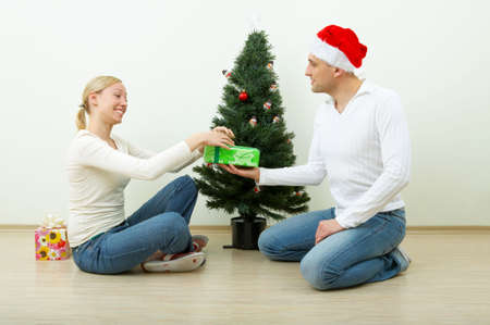 The man gives a gift to the woman against a Christmas pine photo