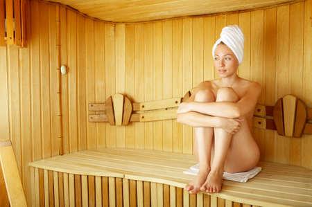 the naked girl: La chica desnuda se sienta en un banco en un sauna