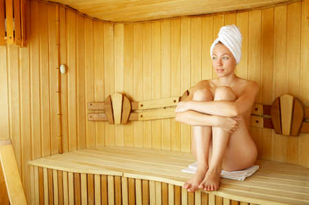 The naked girl sits on a bench in a sauna Stock Photo - 3756800