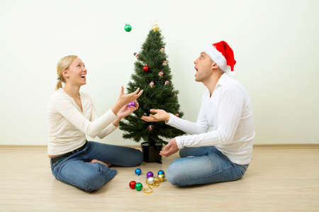 The pair juggles with spheres sitting at a Christmas pine photo