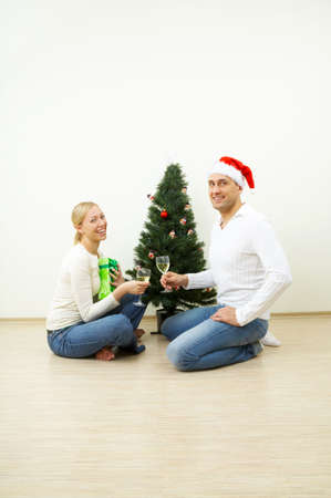 Happy pair at a Christmas pine celebrates photo