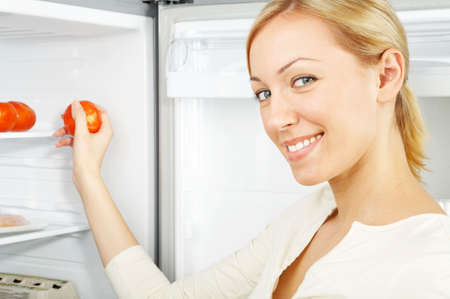 The smiling blonde takes a tomato from a refrigerator Stock Photo - 3790819