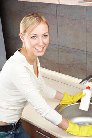 The smiling blonde is engaged in kitchen cleaning