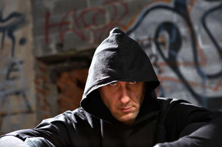 urbanistic: Portrait of the man in a hood against an urbanistic wall Stock Photo