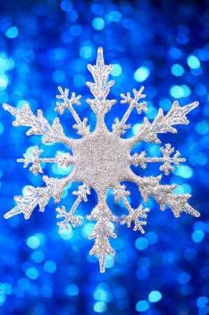 flickering: Plateado copo de nieve sobre un fondo azul parpadeante Foto de archivo
