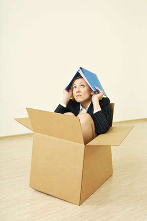 crowded space: The woman in a business suit sitting in a cardboard box