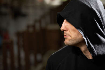 Profile of the man in a hood on a black background