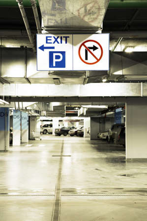 Signs in an underground parking with cars photo