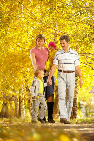 The family with two children walks on autumn park