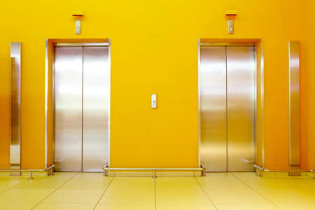 elevator: Photo of an orange hall with two lifts