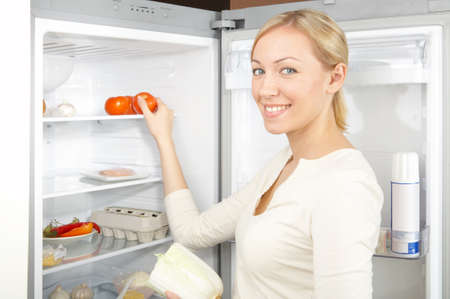 A smiling blonde takes a tomato from a refrigerator Stock Photo - 4124485