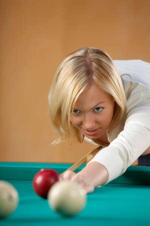 The beautiful blonde aims in a billiard sphere photo