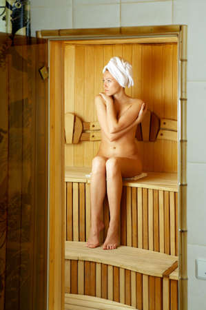The bared girl sits on a regiment in a sauna photo