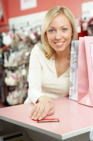 The blonde offers a credit card in shop Stock Photo - 4295486