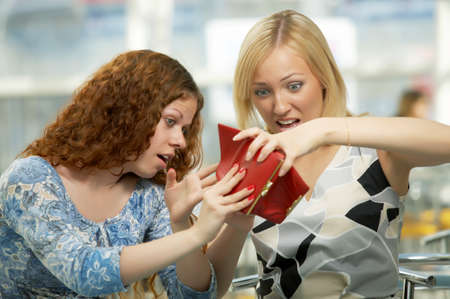 spent: Two girls shake out purse contents in cafe