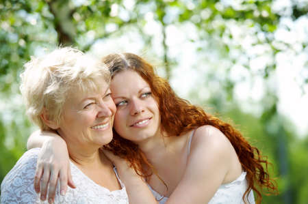 adult offspring: The daughter and elderly mother in a summer garden