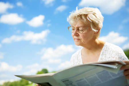 The elderly lady with the newspaper against the sky photo