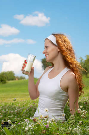 The young girl drinks milk in park against the sky photo