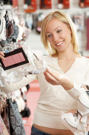 considers: The woman in underwear shop considers a brassiere Stock Photo