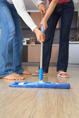 pantalones vaqueros mojados: Dos personas est�n limpiando la casa con una fregona y el mismo