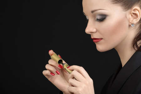 Profile of the beauty opening a tube, on a black background Stock Photo - 4488002