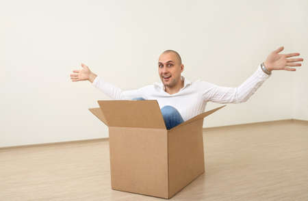 A man is sitting in an empty box in a new flat photo