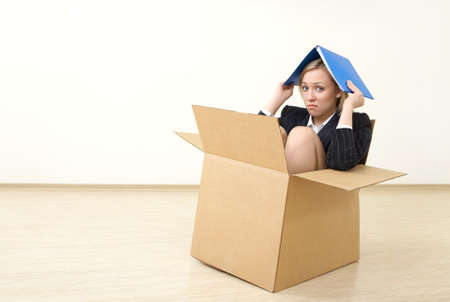 confined: A business woman sits in a box, taking shelter a folder