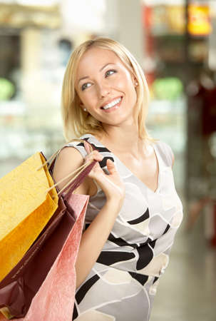 The happy woman in shop with packages through a shoulder
