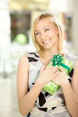 gifts: De lachende blonde is blij persen het ontvangen geschenk aan een borst