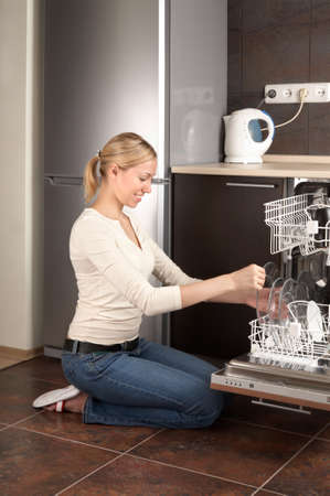 kneeling woman: The blonde sits near to the open dishwasher on kitchen