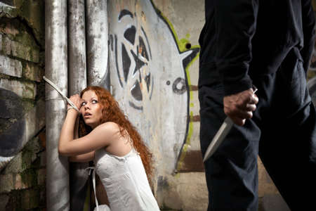 Tied woman is looking at a man with a knife