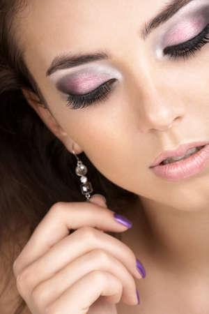 aretes: Un retrato de una mujer joven con los ojos cerrados