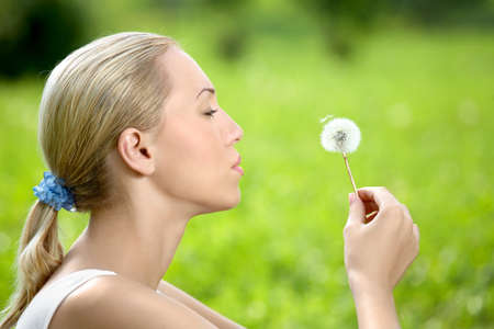 The blonde sits in park on a grass with a dandelion in hands photo