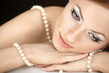 The dreaming woman with a pearl necklace on the bared shoulders
