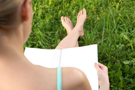 A girl sitting on the grass with a book photo
