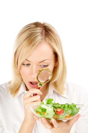 considers: The surprised woman considers through a magnifier the vegetables, isolated