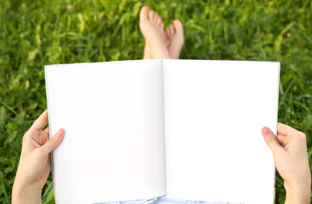magazine reading: Empty spread in female hands against feet and a summer meadow