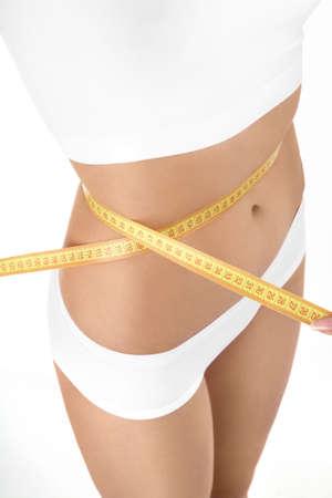 허리의 잘룩 한 선: 흰색 배경에 여성의 허리의 측정을 닫습니다
