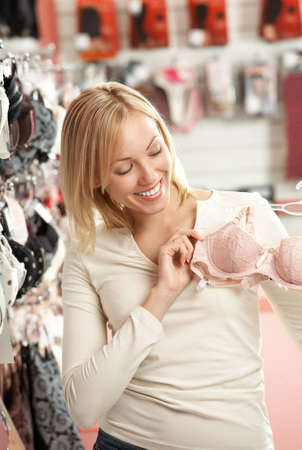 lace bra: The smiling blonde considers a brassiere in shop   Stock Photo