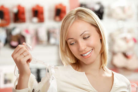 lace bra: The woman looks at a brassiere in shop and smiles