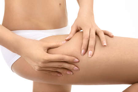 cellulite: Female hands pinch on a hip a skin, isolated