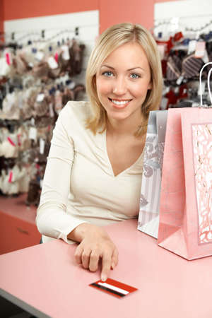 pays: The woman in shop with packages smiles and holds in a hand a credit card Stock Photo