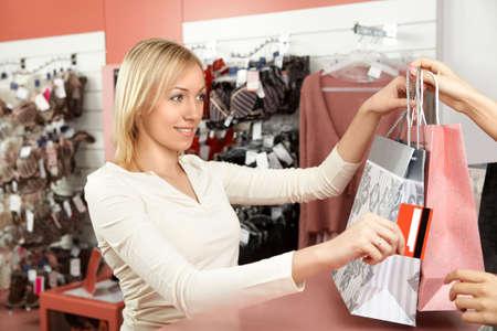 De mooie blonde overdrachten een creditcard aan de verkoper in ondergoed winkel