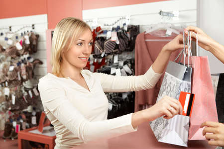 The beautiful blonde transfers a credit card to the seller in underwear shop Stock Photo - 4620787