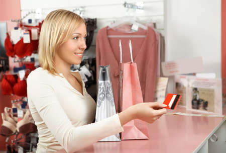 accepting: The blonde with packages in an underwear boutique holds a credit card in a hand