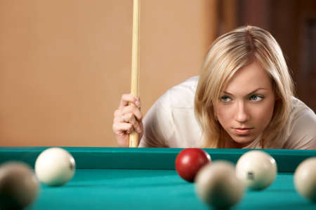 snooker table: The beautiful blonde aims in the course of game at billiards   Stock Photo
